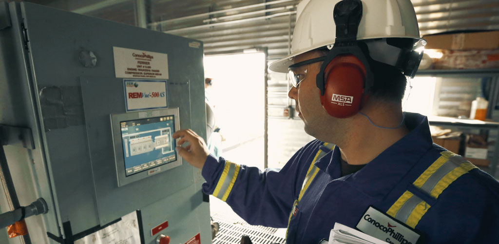 Sean Hiebert, ConocoPhillips Canada's Operations Efficiency Team Lead, showcasing a RemVue 500AS control panel.